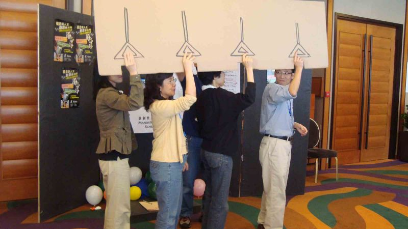 team holding  cardboard sign out of the box creative team building activity