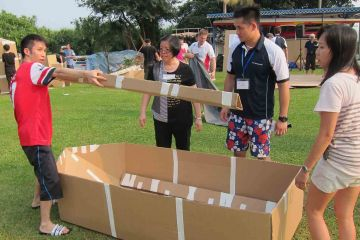 team collaborate to build a cardboard racing boat flat out afloat team building challenge