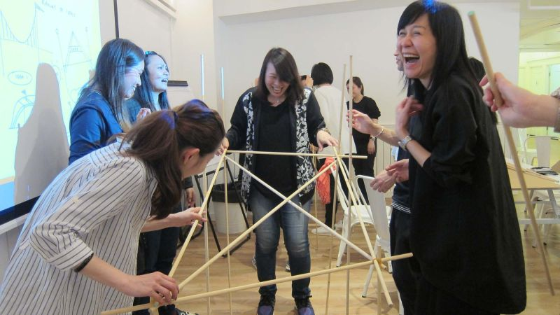women collaborate to complete bridging the divide creative team building activity